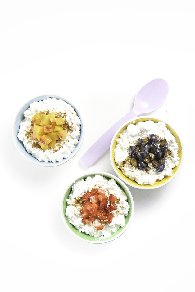 3 small bowls filled with cottage cheese an topped with chunks of fruit are lined up with spoons resting next to each bowl.