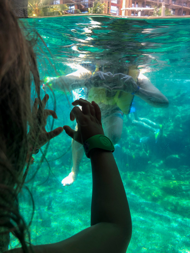 Girl holding hands up in a shape of heart in front of diving take - Disney Aulani