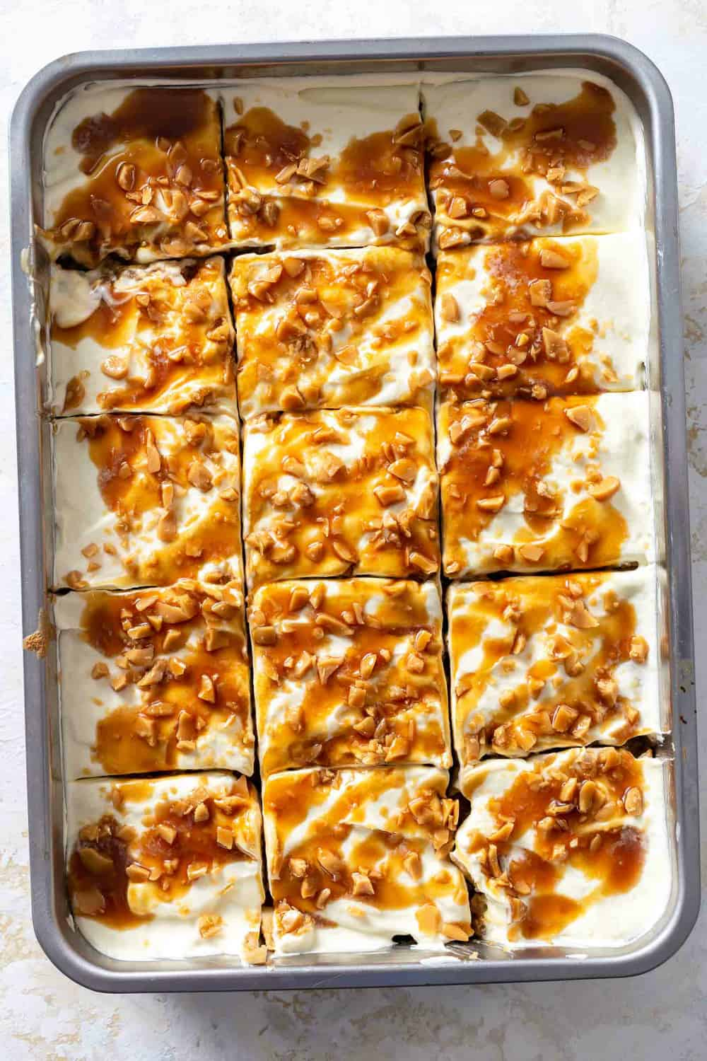 Caramel apple poke cake, sliced in the pan, ready to be served