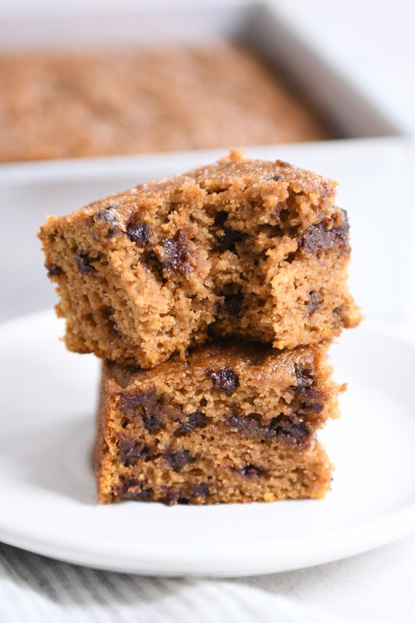 Two pieces of pumpkin chocolate chip snack cake stacked with bite taken out.
