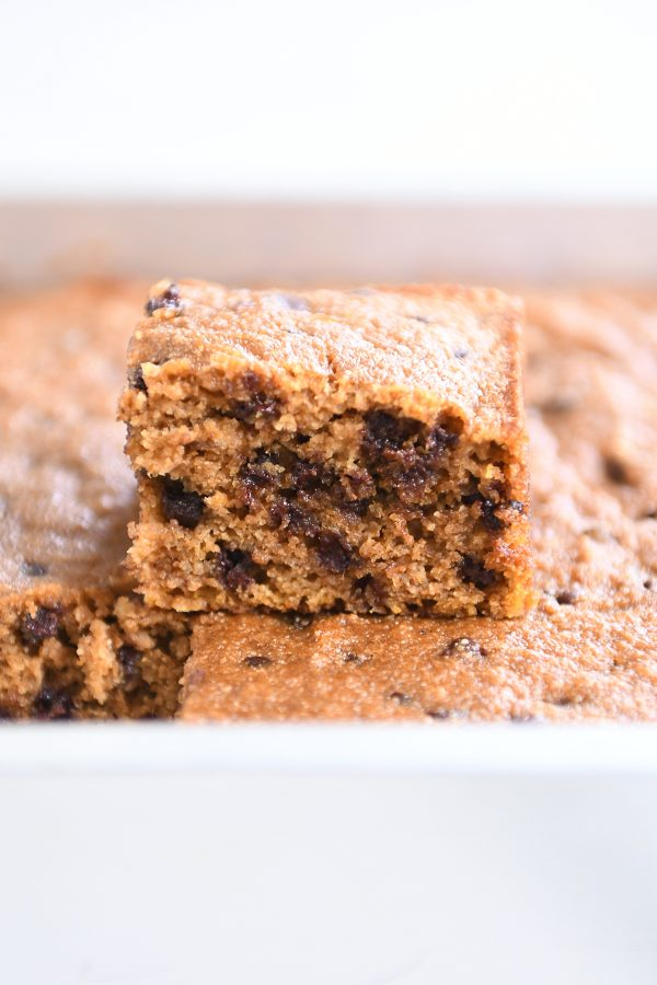 Square piece of pumpkin chocolate chip snack cake on top of baked bars.
