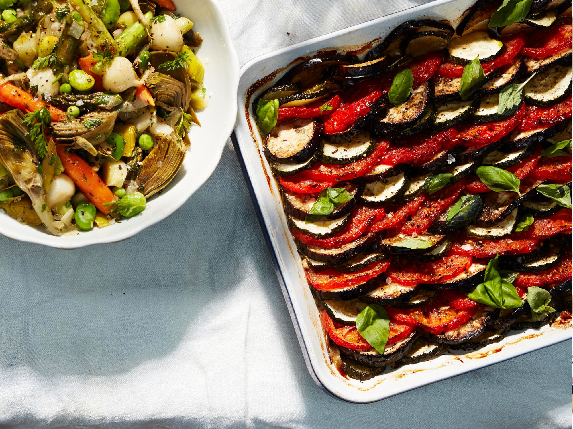 "A tian is a type of gratin, typically vegetables baked in an earthenware dish. (The word ""tian"" also refers to the earthenware dish itself.) This classic Provençal version is made with alternating rows of sliced zucchini, eggplant, and tomato. The flavors meld as the vegetables cook together, somewhat like ratatouille. Seasoned simply with thyme, garlic, and good fruity olive oil, the dish is best served at room temperature. Lulu insists it tastes even better made a day in advance. Get the recipe for <a href=""http://www.saveur.com/provencal-vegetable-gratin-tian-recipe"">Provençal Vegetable Gratin (Tian)</a>"