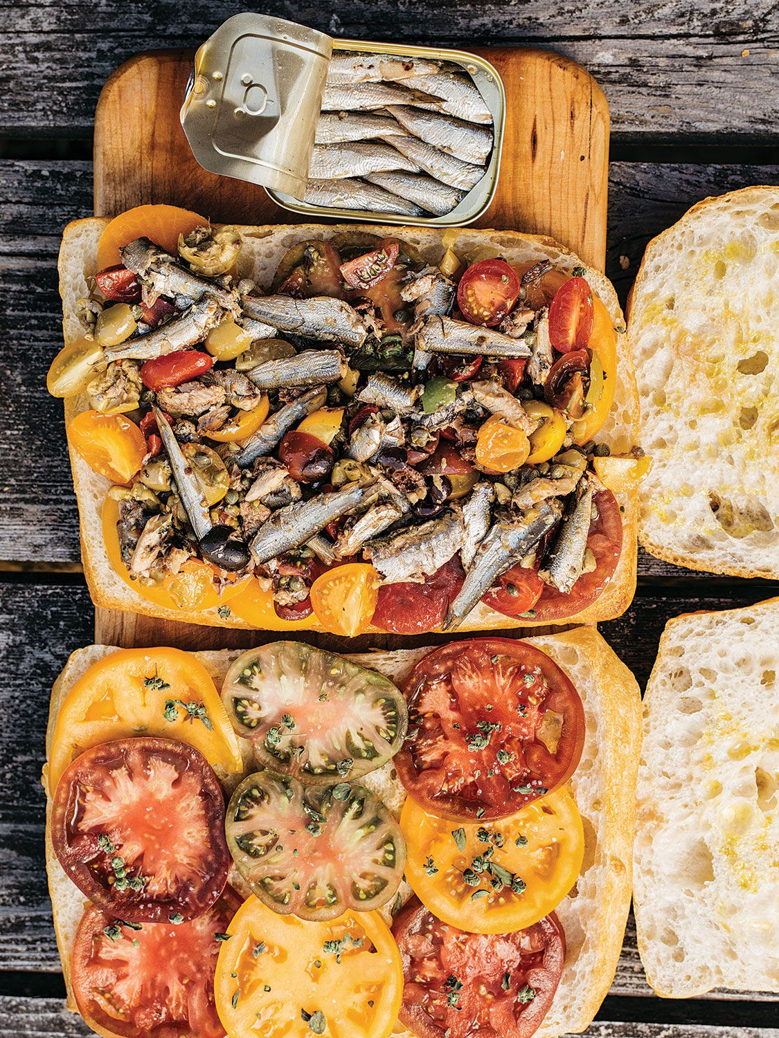 "Cherry tomatoes are tossed with canned sardines here, along with fresh oregano, olives, capers, and a red wine vinaigrette. The whole thing is layered with thin slices of heirloom tomato between slabs of focaccia. Get the recipe for <a href=""https://www.saveur.com/canned-sardine-tomato-and-caper-sandwiches-recipe/"">Canned Sardine, Tomato, and Caper Sandwiches</a>"