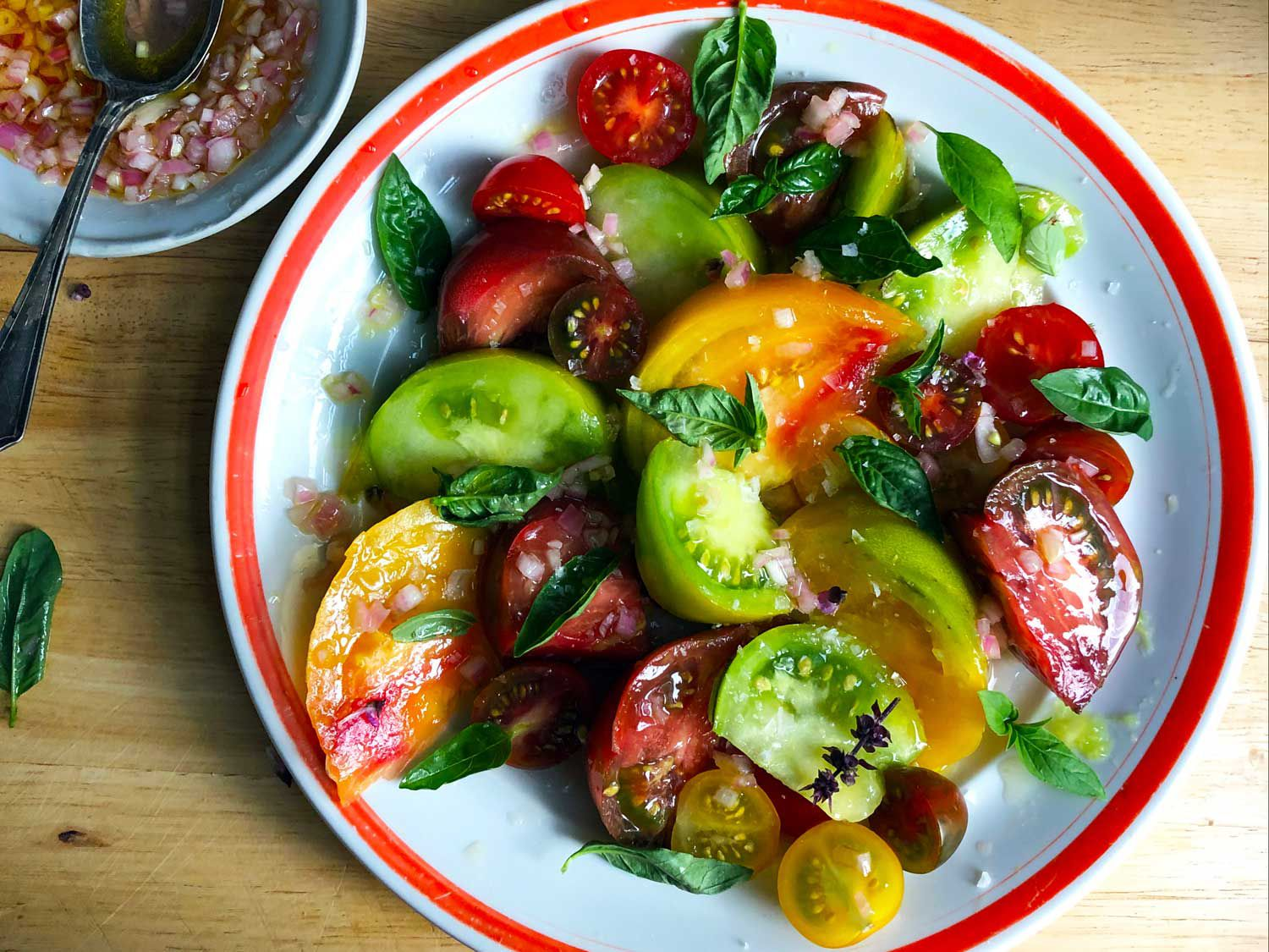"This tomato salad with shallot vinaigrette from Alice Waters is our platonic ideal of the dish. Get the recipe for <a href=""https://www.saveur.com/heirloom-and-cherry-tomato-salad-recipe/"">Heirloom and Cherry Tomato Salad</a>"