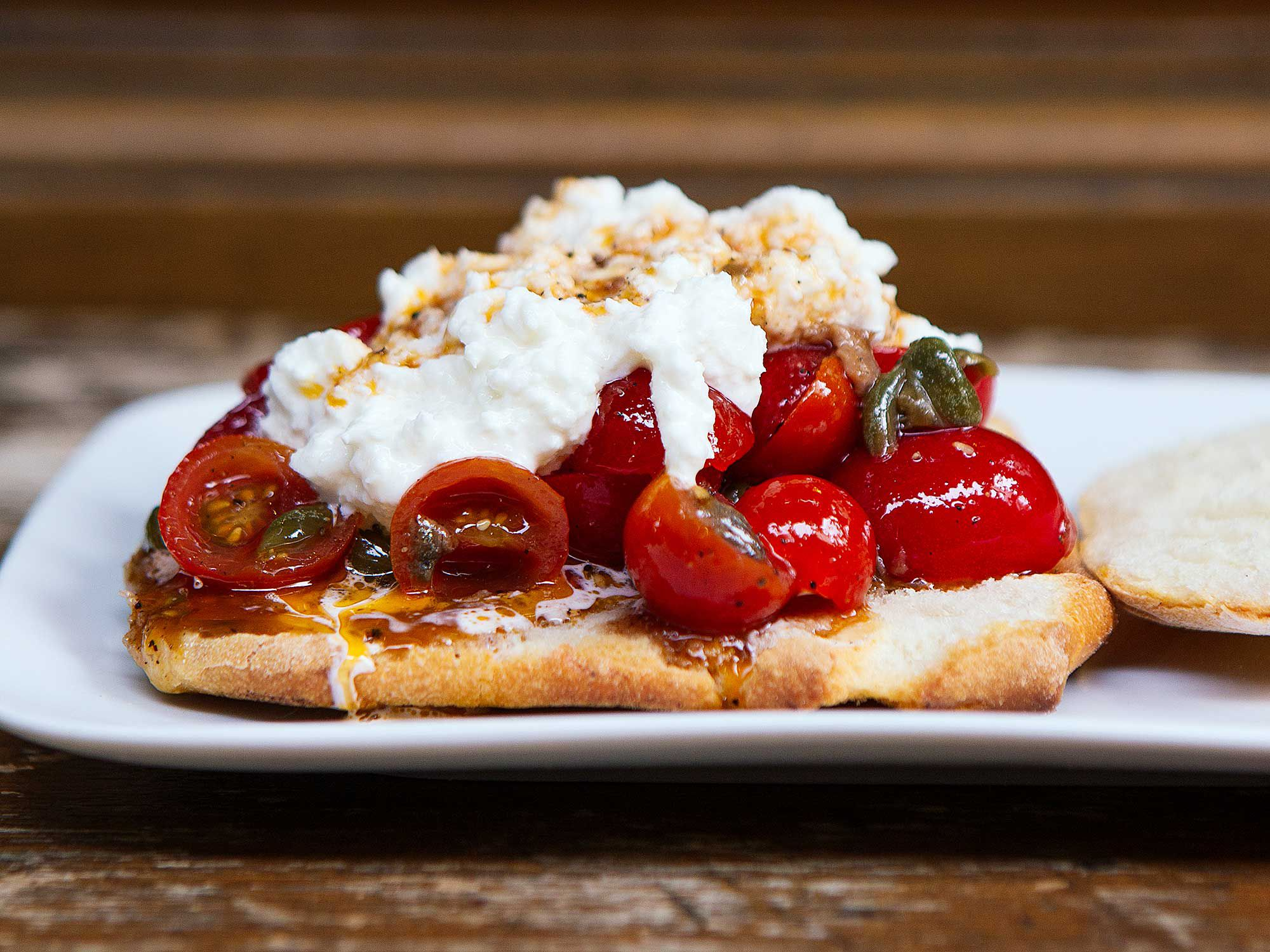 "Crusty bread sops up creamy burrata and juicy marinated tomatoes in this pleasantly messy sandwich. Get the recipe for <a href=""http://www.saveur.com/burrata-tomato-sandwich-italian-recipe"">Burrata and Marinated Cherry Tomato Sandwiches</a>"
