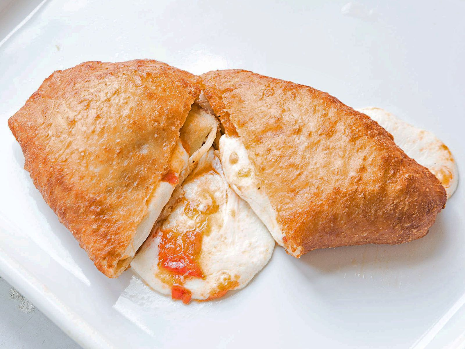 "Italian <em>panzerotti</em> are semi-circular pockets of bread that are usually filled with cheese, deep-fried, and eaten hot. SAVEUR intern Suhashini Sarkar first tried these in Milan; her sister has since developed her own recipe that uses a sauce made from fresh tomatoes. It's reminiscent of pizza, but deep-fried and portable. Get the recipe for <a href=""https://www.saveur.com/fresh-tomato-and-mozzarella-panzerotti-recipe/"">Fresh Tomato and Mozzarella Panzerotti</a>"