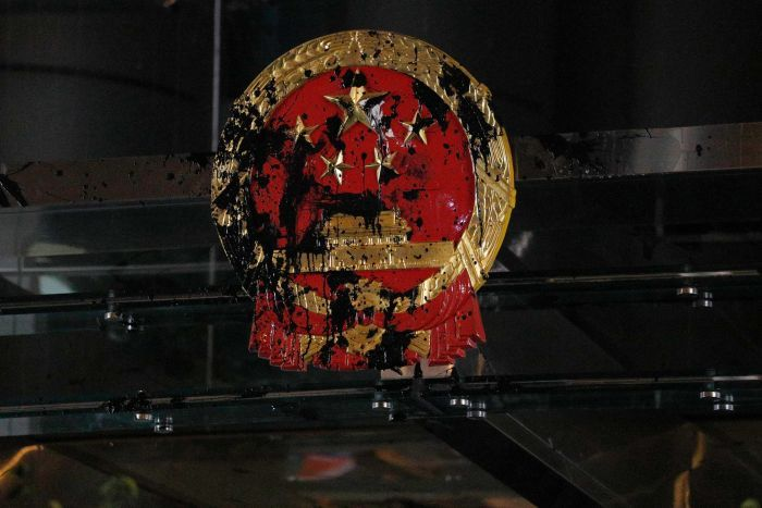 The red and gold National Emblem of the People's Republic of China is shown bolted to a glass office and is smeared in paint.